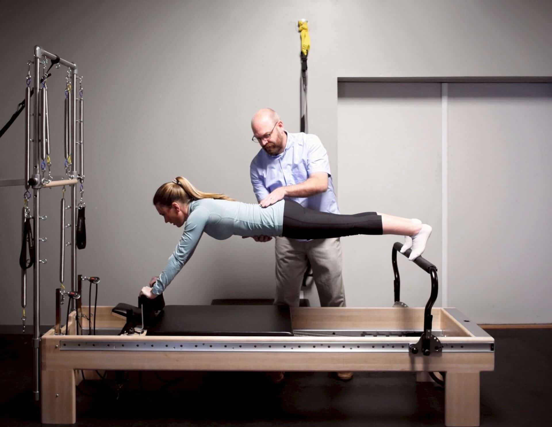Doctor of physical therapy using pilates reformer to help improve posture and core stability.